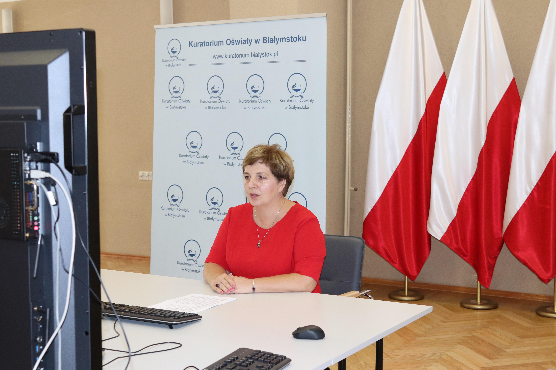 Podlaski kurator oświaty podczas wideokonferencji z dyrektorami. W tle widoczne flagi państwowe oraz baner urzędu. na stole widoczna mysz komputerowa oraz klawiatura.